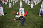 Christian Jacobs, 4, of Hertford, NC lays near the grave of his father, Christopher James Jacobs on Memorial Day at Arlington National Cemetery on Monday May 25, 2015 in Arlington, VA. Christopher was killed in a training accident.  (Photo by Matt McClain/ The Washington Post)