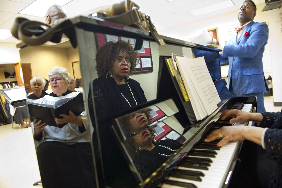 Choir member, Peggy Liggett, left, is reflected in a piano along with organist and assistant senior choir director, Evelyn Simpson-Curenton while visiting performer, Richard Odom sings during a choir rehearsal prior to a Palm Sunday service at Shiloh Baptist Church on Sunday April 13, 2014 in Washington, DC.  Palm Sunday is the beginning to Holy Week, which is the week just prior to Easter Sunday.  (Photo by Matt McClain/ The Washington Post)