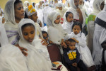 Nattie Kebede, 2, seated at bottom right center, has his head touched by friend, Soliyana Wondwossen, 8, bottom right, during a Holy Thursday service at the Mesrake Isehai Kidus Teklehaymanot Ethiopian Orthodox Tewahedo Church on Thursday April 17, 2014 in Alexandria, VA.  Parishioners feet and hands were washed as part of the service.  (Photo by Matt McClain/ The Washington Post)