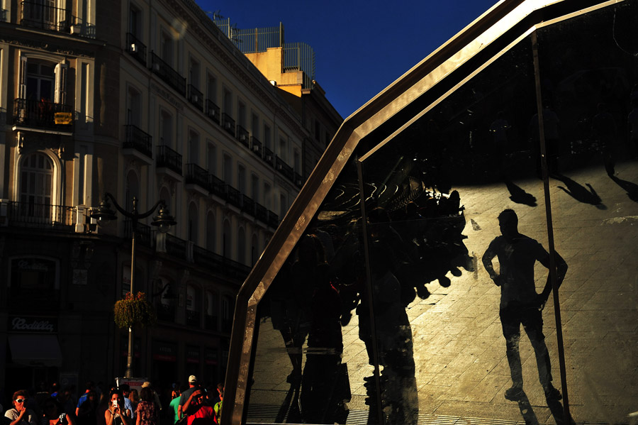 A reflection makes people appear to be towering over a square on Thursday June 13, 2013 in Madrid, Spain.  It's the largest city in Spain.  (Photo by Matt McClain/ The Washington Post)