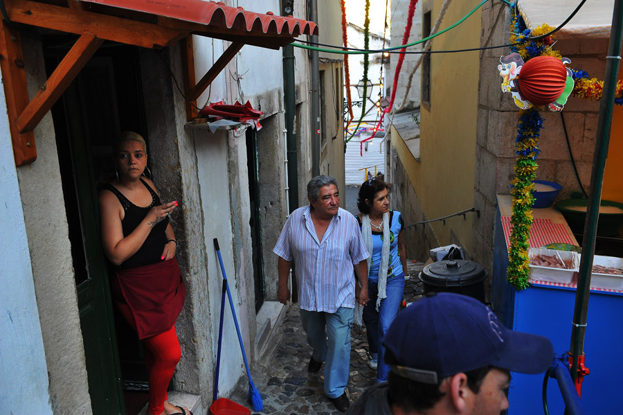 A restaurant worker, left, stands in a doorway as people make their way in the Alfama neighborhood on Wednesday June 5, 2013 in Lisbon, Portugal.  Alfama is Lisbon's oldest section.  (Photo by Matt McClain/ The Washington Post)