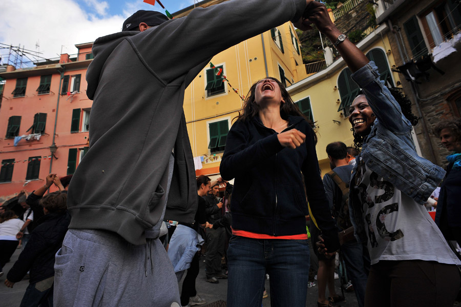People dance as theyand others celebrate the reopening of a business on Sunday May 19, 2013 in Vernazza, Italy.  The area experienced significant damage from a 2011 flood.  (Photo by Matt McClain/ The Washington Post)