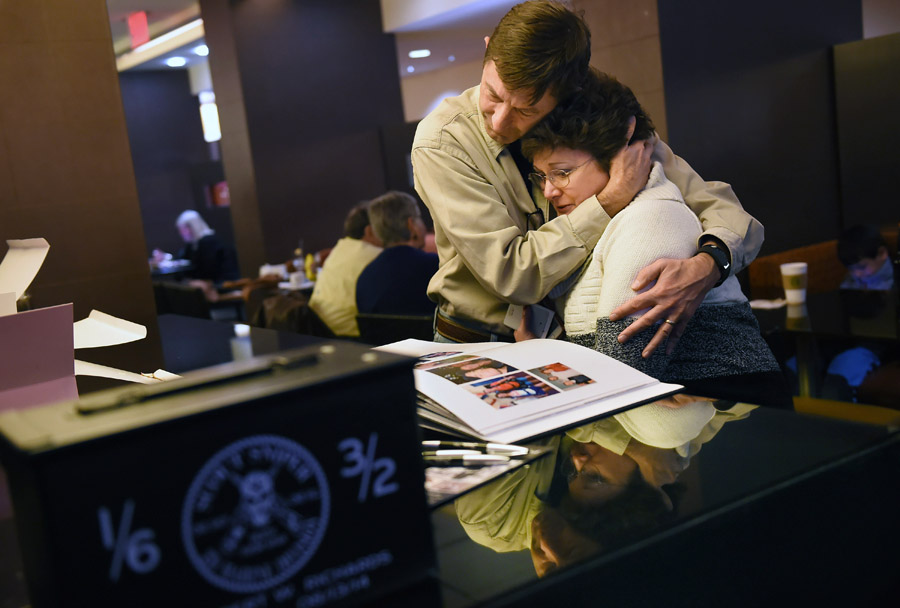 Bill Collins comforts his sister, Cate Richards as she is overcome with emotion while looking at a book of photographs of her son, retired U.S. Marine Robert W. Richards as family and friends gather at the Key Bridge Marriott on the night before an interment service for Richards at Arlington National Cemetery on Thursday February 12, 2015 in Arlington, VA. The ammo box at left contains Robert's ashes. (Photo by Matt McClain/ The Washington Post)
