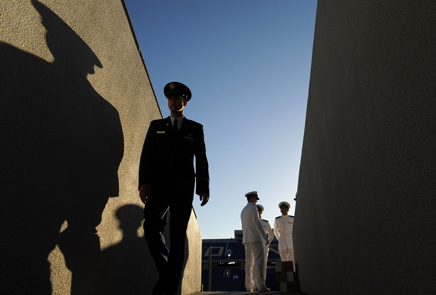 Ushers, right, stand at the end of a tunnel as a person walks through before the beginning of the United States Naval Academy graduation and commissioning ceremony at Navy-Marine Corps Memorial Stadium on Friday May 23, 2014 in Annapolis, MD.  United States Secretary of Defense, Chuck Hagel spoke at the event.  (Photo by Matt McClain/ The Washington Post)