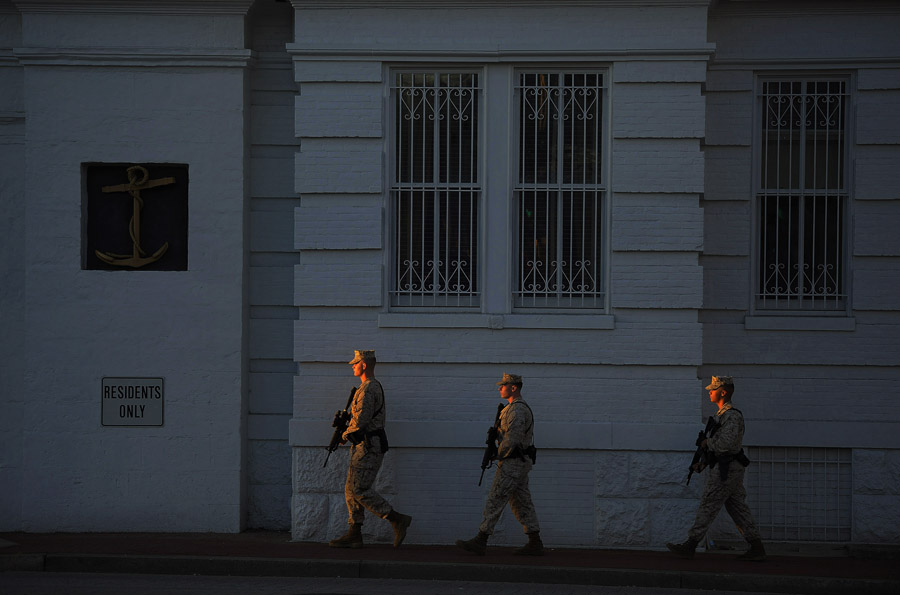 Military personnel walk by the Washington Navy Yard on Wednesday September 18, 2013 in Washington, DC.  A mass shooting occurred there Monday.  (Photo by Matt McClain/ The Washington Post)