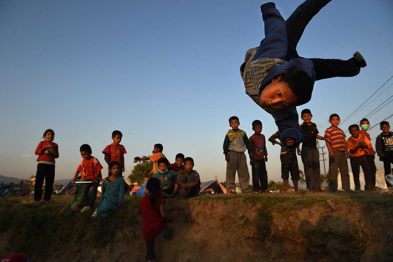 A young boy does a flip into a pit that was being used for garbage at a tent encampment for people displaced by the earthquake on Tuesday May 05, 2015 in Kathmandu, Nepal. A deadly earthquake has killed thousands in Nepal. (Photo by Matt McClain/ The Washington Post)
