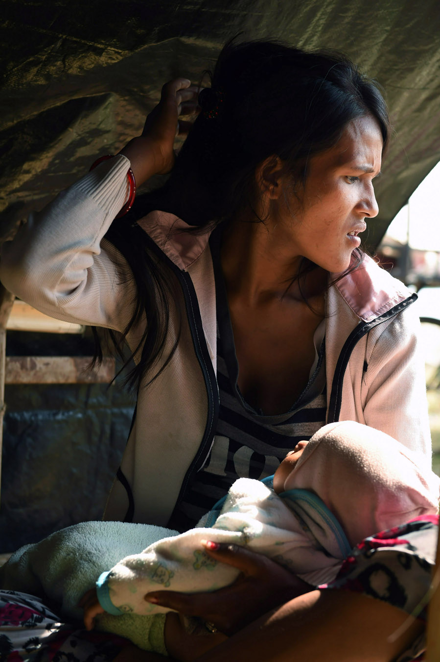 Widowed and displaced by the earthquake, Minu Nepali, 23, holds her unnamed youngest son as she now lives in a tent encampment on Tuesday May 05, 2015 in Kathmandu, Nepal. Her husband was killed in the earthquake that has killed thousands in Nepal. (Photo by Matt McClain/ The Washington Post)