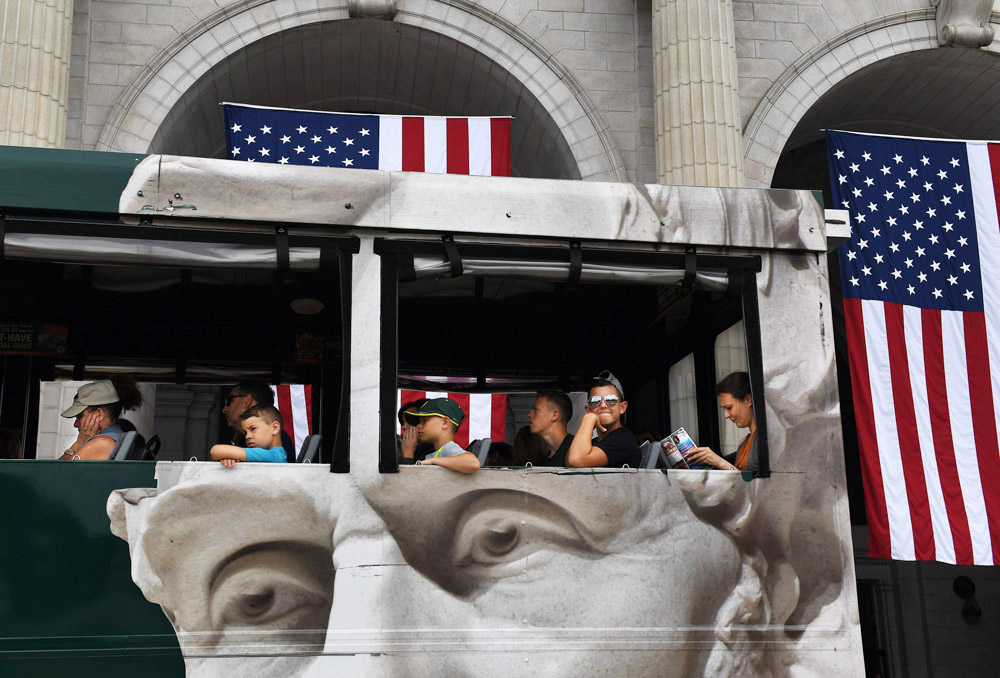 A sightseeing bus passes by American flags decorating Union Station on Sunday July 03, 2016 in Washington, DC. Monday is the Fourth of July. A strong chance of rain is being forecasted for the Washington, DC area on Monday. (Photo by Matt McClain/ The Washington Post)