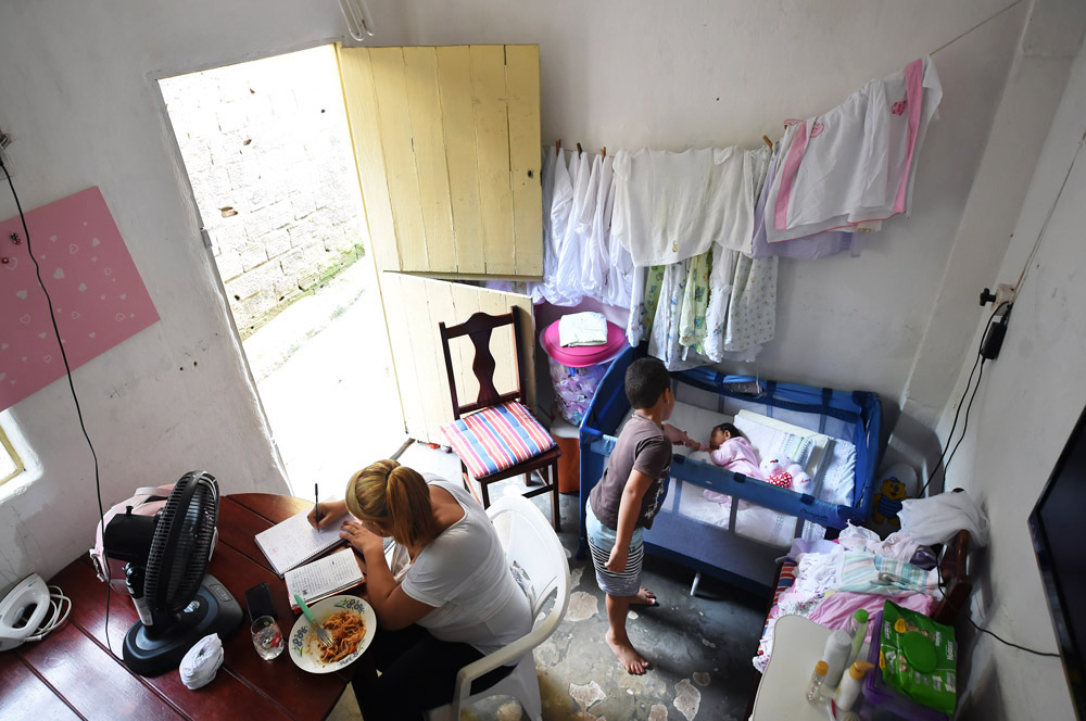Severina Carla da Silva, eats while writing down song lyrics as her son, Nicolas Davi Silva, 5, looks at his sister, Nivea Heloise Silva at their home on Tuesday March 15, 2016 in Recife, Brazil. Nivea was born with microcephaly. The Zika virus has been linked to the condition. (Photo by Matt McClain/ The Washington Post)