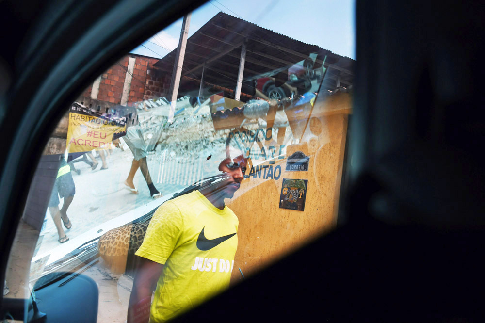A man walks along a sidewalk as others are reflected in a vehicle's window on Sunday March 13, 2016 in Recife, Brazil. The Zika virus has been rampant in this region. The virus is spread by the Aedes aegypti mosquito. (Photo by Matt McClain/ The Washington Post)