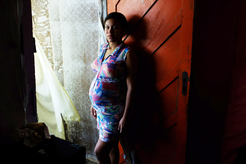 Jessica Thalia Cruz Menezes poses for a portrait at her home in a community along the water on Sunday March 13, 2016 in Recife, Brazil. Jessica is eight months pregnant and has had no signs of the Zika virus. The Zika virus has been rampant in this region. The virus is spread by the Aedes aegypti mosquito. Trash and stagnant water are breeding grounds for mosquitos. (Photo by Matt McClain/ The Washington Post)