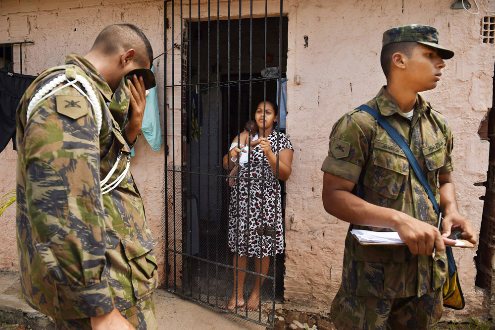 Tatiana Alves holds her one month old baby, Joao Pedro Alves as she speaks with members of the Brazilian military as they go door to door along with health care workers in a favela to talk to residents about the threat of Zika virus, dengue fever and chikungunya on Saturday March 12, 2016 in Recife, Brazil. The Zika virus has been rampant in this region. The virus is spread by the Aedes aegypti mosquito. (Photo by Matt McClain/ The Washington Post)
