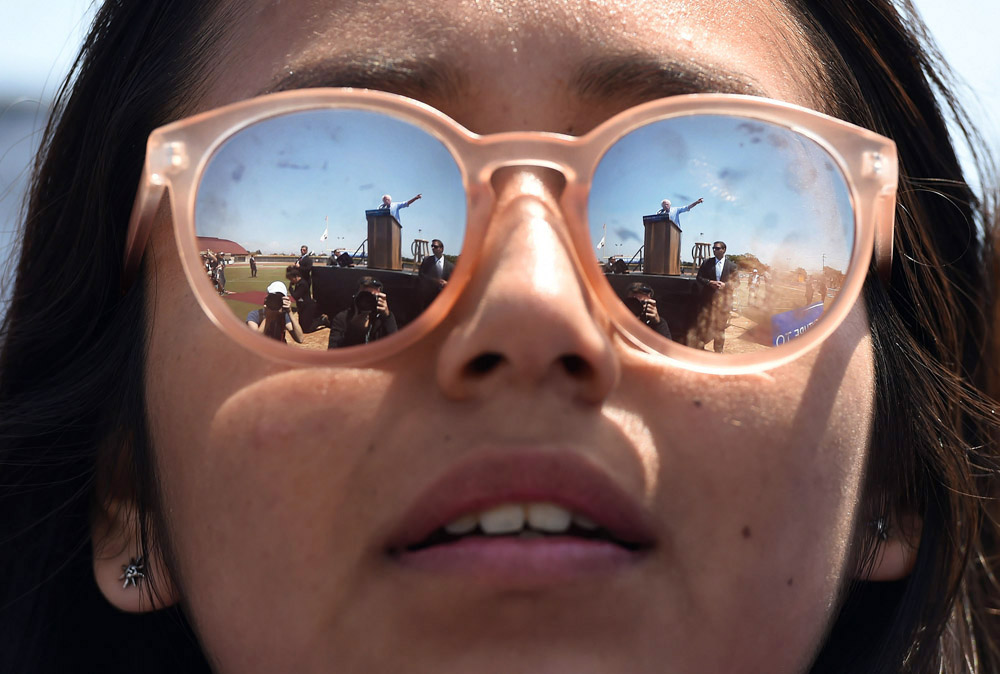 Presidential candidate, Bernie Sanders reflected in the sunglasses of Daisi Hernandez, 18, as he speaks at a rally at Santa Maria High School on Saturday May 28, 2016 in Santa Maria, CA. The primary in California is June 7th. (Photo by Matt McClain/ The Washington Post)
