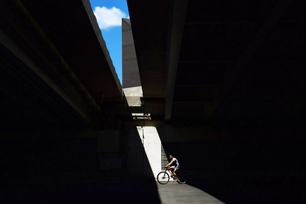 A bicyclist is illuminated as he rides under the Woodrow Wilson Memorial Bridge on Sunday August 7, 2016 in Alexandria, VA. (Photo by Matt McClain/ The Washington Post)