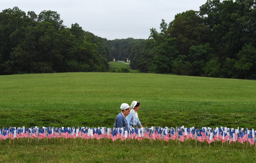 Mount Vernon employees, Kathrin Breitt Brown, left center, and Eryn Landry, walk behind American flags during Fourth of July festivities at Georg Washington's Mount Vernon on Monday July 04, 2016 in Mount Vernon, VA. (Photo by Matt McClain/ The Washington Post)