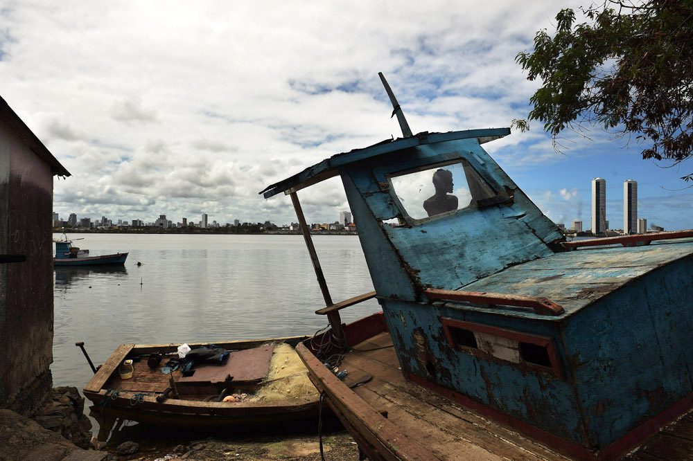 A man is seen on a boat along the shoreline on Tuesday March 22, 2016 in Recife, Brazil. The Zika virus is rampant in the region. The virus is spread by the Aedes aegypti mosquito. (Photo by Matt McClain/ The Washington Post)