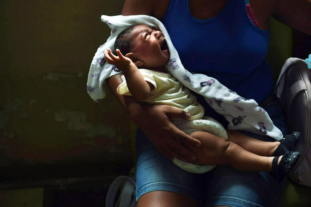 Micaela de Souza Celestino holds her daughter, Annika Vitoria Medeiros da Silva at Hospital das Clinicas da Universidade Federal de Pernambuco on Monday March 14, 2016 in Recife, Brazil. Annika was born with microcephaly, which the Zika virus is being linked to. The virus has been rampant in this region. It is spread by the Aedes aegypti mosquito. (Photo by Matt McClain/ The Washington Post)