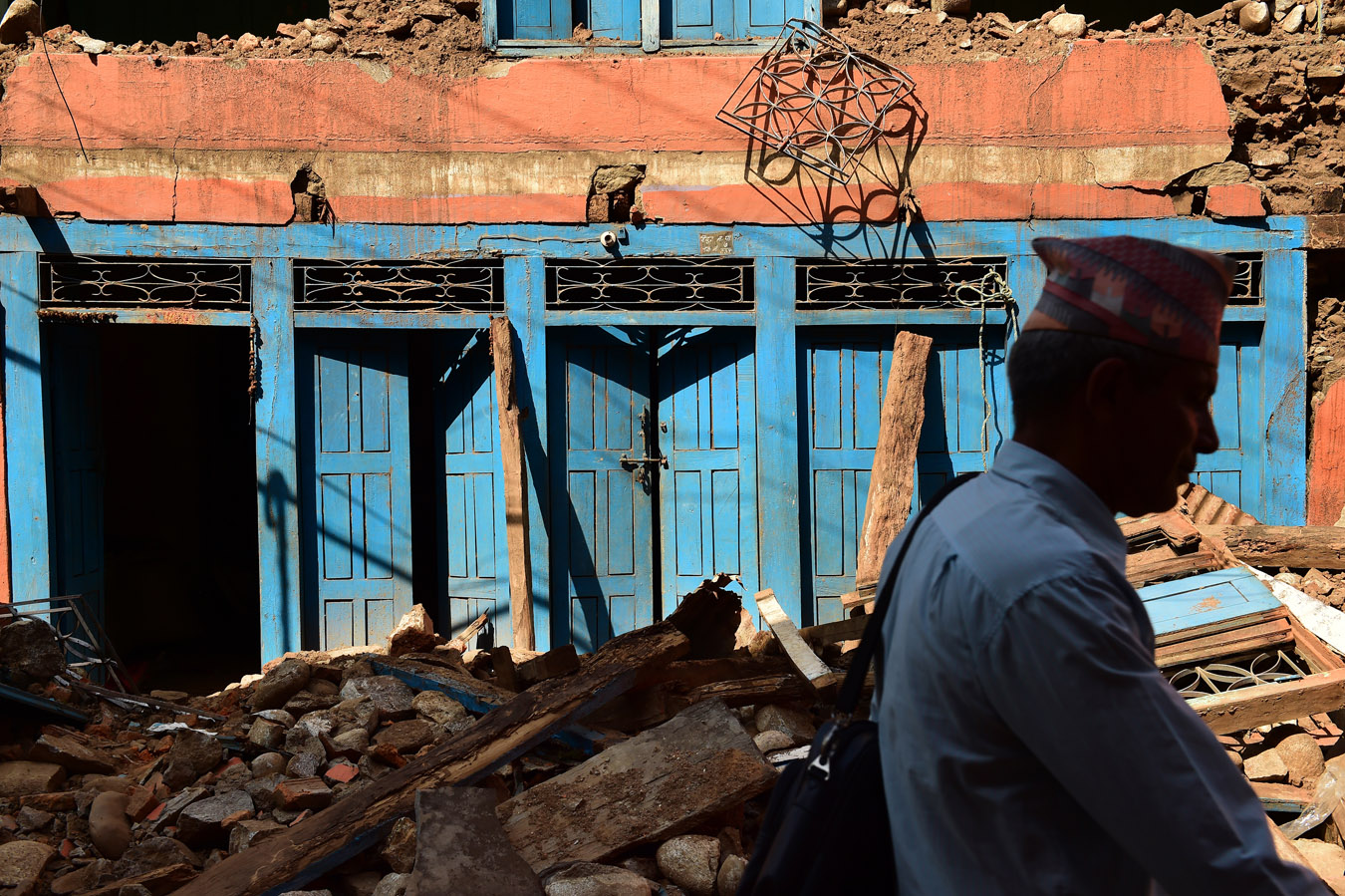 A man walks an earthquake damaged building on Sunday May 03, 2015 in Devighat, Nepal which is located in the Nuwakot District. A deadly earthquake in Nepal has killed thousands. (Photo by Matt McClain/ The Washington Post)