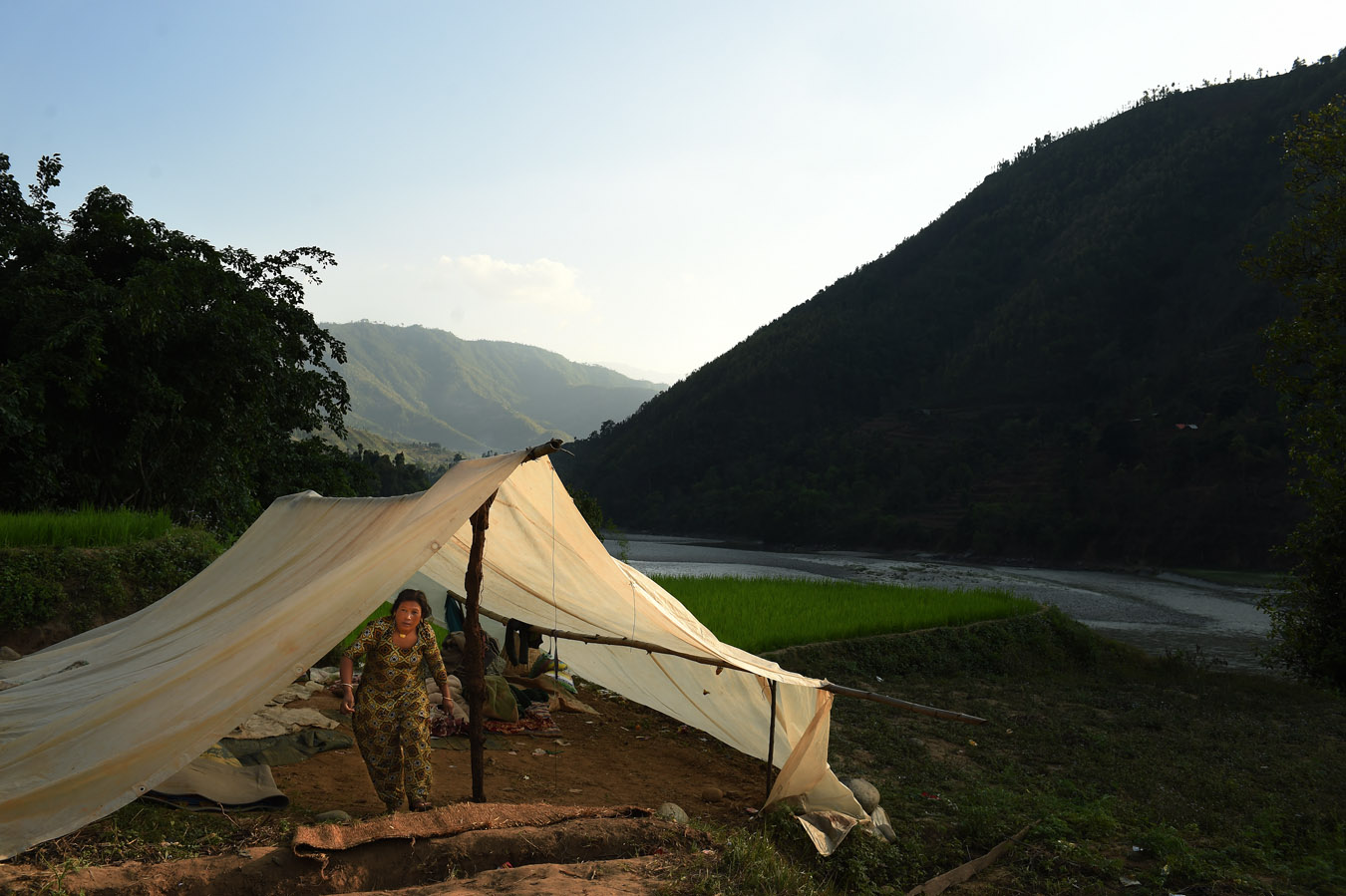 A woman walks out of a tent nestled in a scenic spot on Sunday May 03, 2015 in the Nuwakot District of Nepal. A deadly earthquake in Nepal has killed thousands. Tent encampments are a common sight as people have lost their homes or are afraid to return to them because of earthquake damage. (Photo by Matt McClain/ The Washington Post)