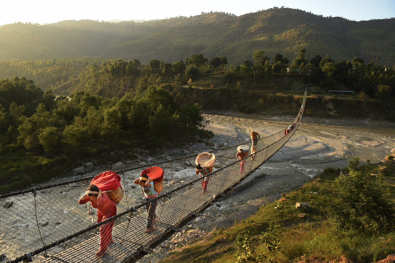 People cross a bridge on Sunday May 03, 2015 in the Nuwakot District of Nepal. A deadly earthquake in Nepal has killed thousands. (Photo by Matt McClain/ The Washington Post)