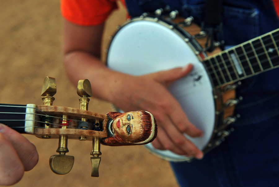 Chris Testerman, bottom left, and Robbie Anders, right, rehearse before performing during the Old Fiddlers' Convention at Felts Park on Friday August 09, 2013 in Galax, VA.  This was the 78th year of the event.  (Photo by Matt McClain/ The Washington Post)