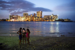Beach goers are illuminated by a phone on Saturday July 04, 2015 in San Juan, Puerto Rico. (Photo by Matt McClain/ The Washington Post)