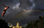 A rainbow extends over the state capitol as Destiny Caceres, 10, of Albuquerque, New Mexico leaps from the Stunt Jump attraction Saturday 06/05/10 during People's Fair at Civic Center Park in downtown Denver, Colo. Photo by Matt McClain