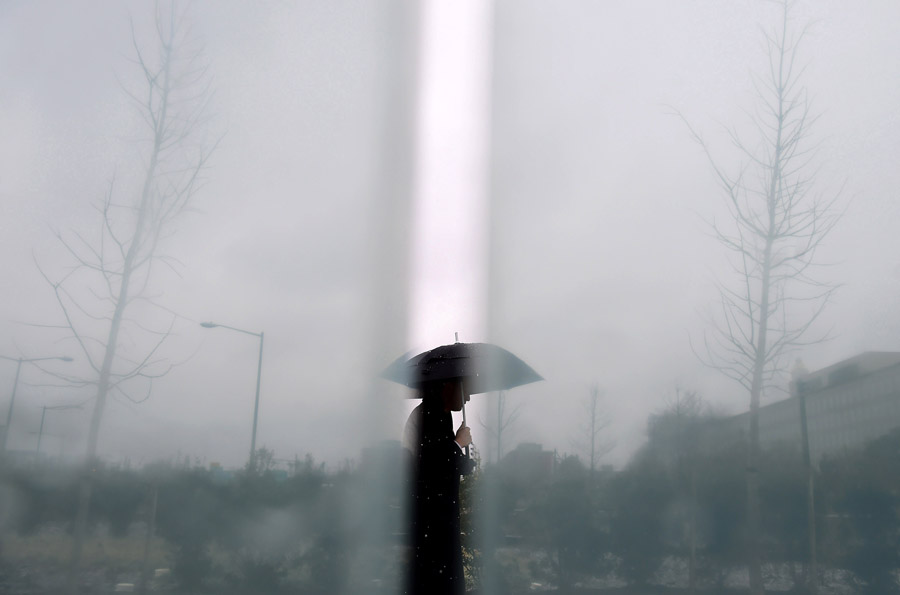 An umbrella clad pedestrian is framed between panels as he walks by the American Veterans Disabled for Life Memorial as it lightly snows on Monday January 26, 2015 in Washington, DC. (Photo by Matt McClain/ The Washington Post)