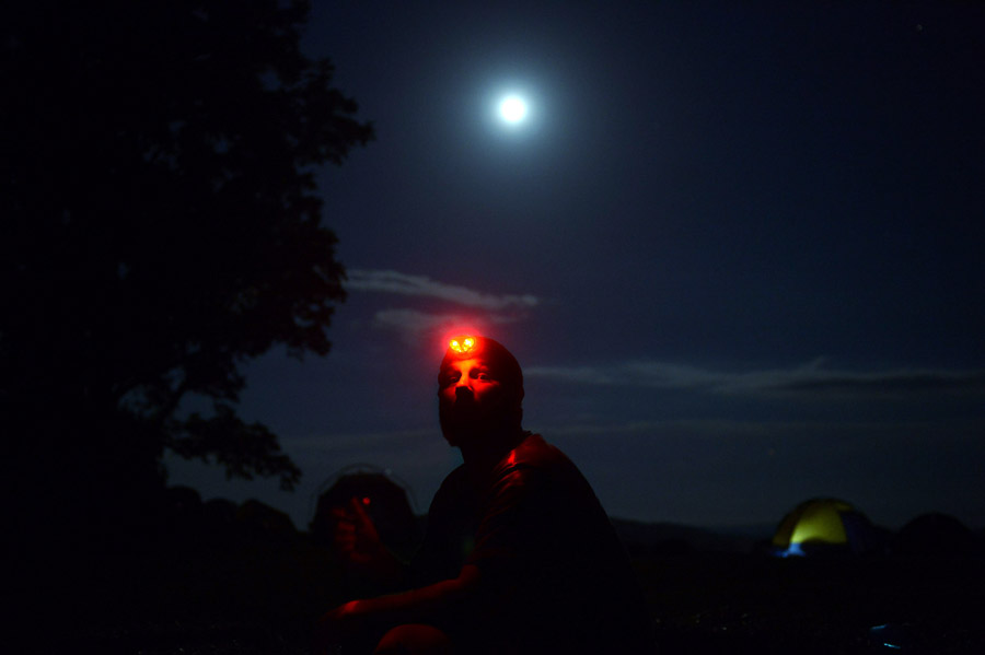 The moon shines bright as Frank Schwartz, 22, sits near a campfire at Sky Meadows State Park during the Great American Backyard Campout event on Saturday June 22, 2013 in Delaplane, VA.  Schwartz works as an intern at the park.      (Photo by Matt McClain/ The Washington Post)
