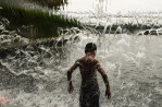 A boy cools off from the heat under a waterfall feature at the Yards Park on Thursday August 21, 2014 in Washington, DC.  (Photo by Matt McClain/ The Washington Post)