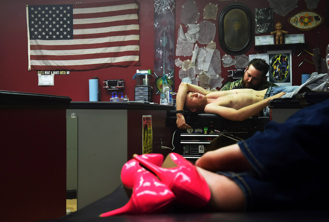 Steve Cherry, top right, or Riff Raff as he is known tattoos SPC Caleb McKinnon as he and his wife, Savannah McKinnon, bottom, get similar tattoos at Black Kat Tattoo on Saturday November 08, 2014 in Clarksville, TN.  McKinnon was deploying to Afghanistan the next day from Fort Campbell.  (Photo by Matt McClain/ The Washington Post)