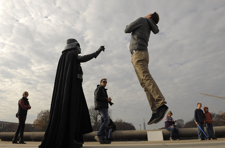 Roman Flaig, right, jumps in the air as he has his photograph taken with Rob Davis of Glen Burnie, MD, left, as he wears a Darth Vader costume near the United States Capitol on Sunday December 01, 2013 in Washington, DC.  Davis and others were promoting the Museum of Science Fiction.  Flaig jumped in order to make it look as if he was in the clutches of Darth Vader.  (Photo by Matt McClain/ The Washington Post)