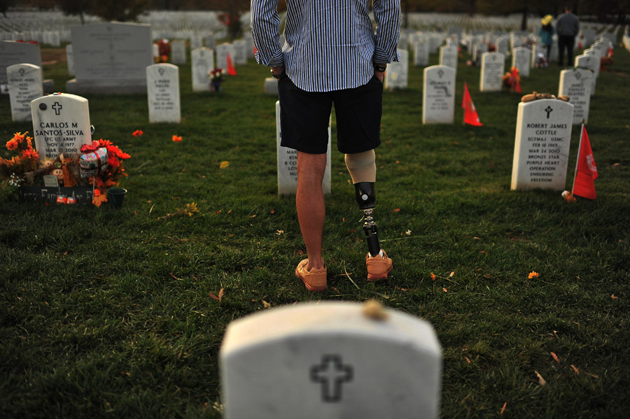 Matthew White of Washington, DC visits the grave of U.S. Army Staff Sergeant Scott W. Brunkhorst at Arlington National Cemetery on Sunday November 11, 2012 in Arlington, VA.  White served with Brunkhorst.  Scott died in 2010 while serving in Afghanistan.  President Barack Obama visited Arlington National Cemetery on Sunday in honor of Veterans Day.  (Photo by Matt McClain for The Washington Post)
