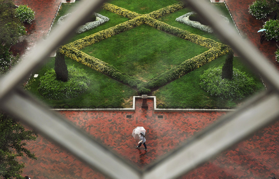 Viewed from a window of the Smithsonian Institution Building or the Smithsonian Castle an umbrella clad pedestrian makes their way by the Enid A. Haupt Garden on Wednesday September 28, 2016 in Washington, DC. (Photo by Matt McClain/ The Washington Post)
