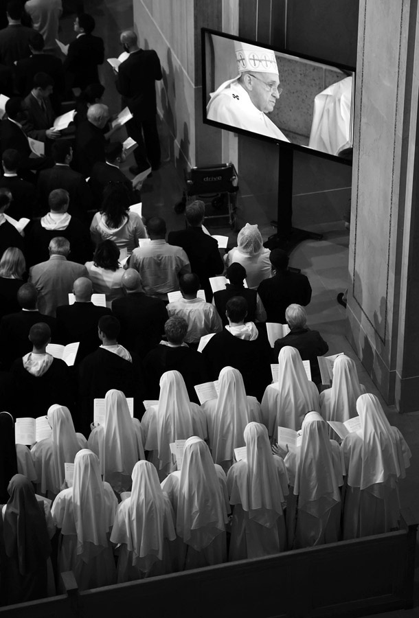 Attendees within the Basilica of the National Shrine of the Immaculate Conception watch Pope Francis on screens as he leads a mass outside on Wednesday September 23, 2015 in Washington, DC. (Photo by Matt McClain/The Washington Post)