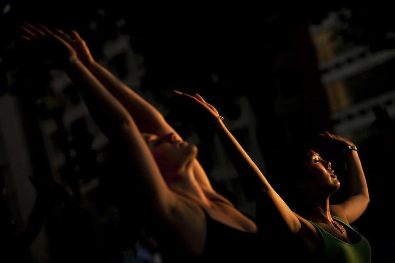 Alexandra Scott, left, and Yukari Usuda, right, are bathed with late afternoon light as they take part in {quote}Yoga in the Park{quote} at Dupont Circle which is sponsored by Lululemon Athletica on Wednesday September 05, 2012 in Washington, DC.  (Photo by Matt McClain for The Washington Post)
