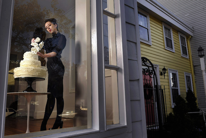 Maggie Austin LaBaugh of Maggie Austin Cake poses for a portrait with a three tier ivory frill cake with sugar roses at her new location on Thursday November 3, 2011 in Alexandria, VA.  LaBaugh is a former ballerina turned cake designer.  She danced for the Joffrey Ballet in Chicago, IL.  (Matt McClain for the Washington Post)