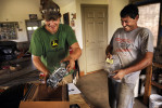 Zach Orndorff, 18, left, and his father, Bill Orndorff react to unwrapping a carburetor they received by delivery on Thursday August 23, 2012 in Woodstock, VA.  The carburetor was used in Bill's demolition derby car.
