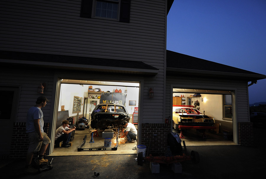 Zach Orndorff, left, and his brother, Josh Orndorff, left center, watch their father Bill Orndorff, center, work on Zach's demolition derby car at the family's Woodstock, VA home on Tuesday August 21, 2012 in Woodstock, VA.