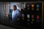 Carl C. Johnson, 90, is reflected in a display of his military medals as he poses for a portrait at his home on Monday August 22, 2016 in Ashburn, VA. Johnson was a member of the famed, Tuskegee Airmen. (Photo by Matt McClain/ The Washington Post)