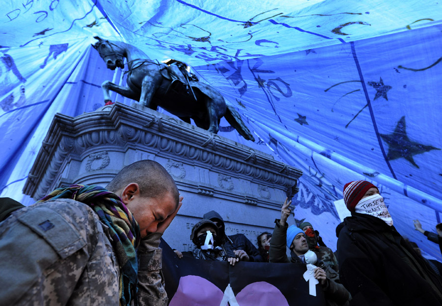 Michael Patterson, left, and other Occupy DC protesters are seen under a tarp covering the statue of Major General James McPherson in McPherson Square on Monday January 30, 2012 in Washington, DC.  The National Park Service issued a noon deadline to enforce no-camping regulations in McPherson Square and Freedom Plaza.  (Photo by Matt McClain for The Washington Post)