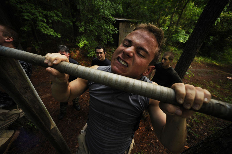 Jon Vegh, 18, of Long Beach, NY strains to do pull-ups while taking part in the Extreme SEAL Experience on Tuesday May 17, 2011 in Chesapeake, VA.  Men from around the country paid money to learn techniques used in Navy SEAL training.  (Photo by Matt McClain/For The Washington Post)