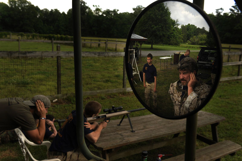Retired Navy SEAL, Don Shipley, right, watches as participants fire weapons while taking part in the Extreme SEAL Experience, which is run by Shipley on Wednesday May 18, 2011 in Chesapeake, VA.  Men from around the country paid money to learn techniques used in Navy SEAL training.   (Photo by Matt McClain/For The Washington Post)