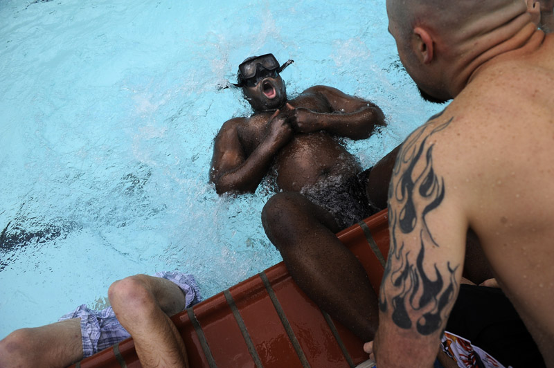 John Speaker, 35, of Texas, right, holds the ankles of Darion Brown, 36, of California as he does sit-ups in a pool while taking part in the Extreme SEAL Experience on Wednesday May 18, 2011 in Chesapeake, VA.  Men from around the country paid money to learn techniques used in Navy SEAL training.   (Photo by Matt McClain/For The Washington Post)