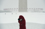 A woman walks near the Washington Monument on Saturday January 23, 2016 in Washington, DC. A large snow event was being predicted for Washington, DC area. (Photo by Matt McClain/ The Washington Post)