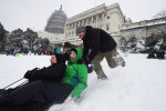 Jenny Isely, left, and Anna McDonagh, center, are pushed by Seth McDonagh, and Mark Iozzi, right, outside the U.S. Capitol on Saturday January 23, 2016 in Washington, DC. A large snow event was being predicted for Washington, DC area. (Photo by Matt McClain/ The Washington Post)
