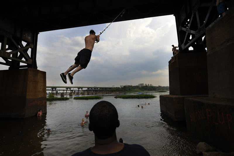 Thomas Johnson of King William, VA watches Justin Bryant of Mechanicsville, MD swing into the James River on Wednesday July 18, 2012 in Richmond, VA.  (Photo by Matt McClain for The Washington Post)