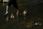 Stuart Sherbs, top, uses a rope swing to lauch himself towards the water to join Mica D'Alesandro, center left to right, Jessica Huskey, Connor Eash, Chris Winter, Sean Winter, and Bekah Hogg as people cool off from the summer heat in the Patapsco River in Carroll County, MD on Monday July 16, 2012.  (Photo by Matt McClain for The Washington Post)