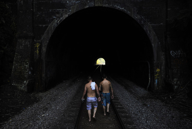 Cody Yeagle, center left, and Mike Bretado, center right, walk towards the Henryton Tunnel while leaving a swimming hole in the Patapsco River in Carroll County, MD on Monday July 16, 2012.  Swimmers walk through the tunnel to get from one well known swimming hole to another.  The tunnel was constructed in the mid-1800's by the Baltimore and Ohio Railroad.  It has gone through some changes since then, including being rebuilt in 1903.  It is still in use today.  (Photo by Matt McClain for The Washington Post)