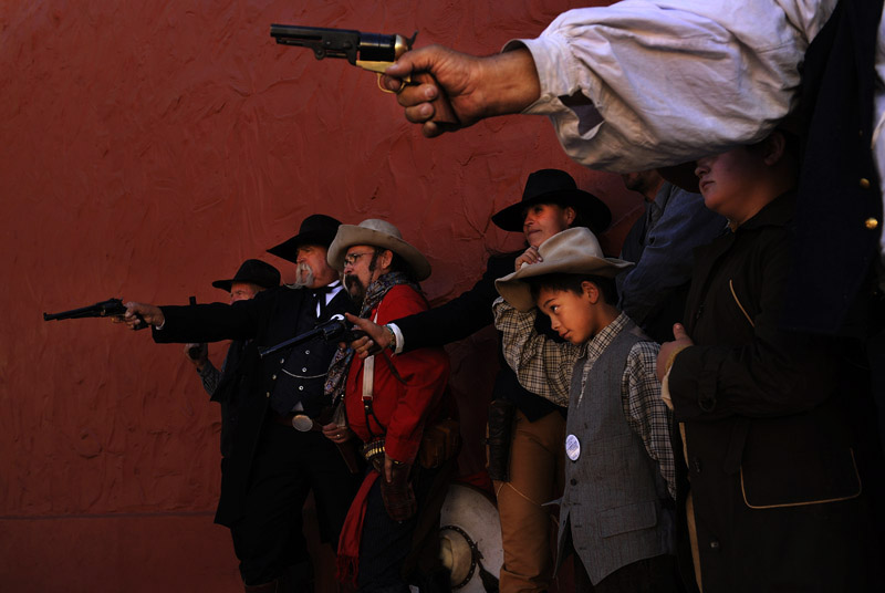 Ronald Cruz, 10, center, adjusts his hat as he and others with the Shadow Riders pose for a photograph during Wyatt Earp Days on Saturday May 26, 2012 in Tombstone, AZ.  The event featured street gunfights and a costume contest among other entertainment. The town was made famous by the Gunfight at the O.K. Corral.  Once a thriving mining town, Tombstone lives on now by retelling the stories of its past.  (Photo by Matt McClain for The Washington Post)